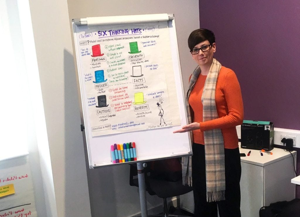 """Natasha, a management apprentice, performs a demonstration on the """"six thinking hats"""" at a management and leadership workshop"""